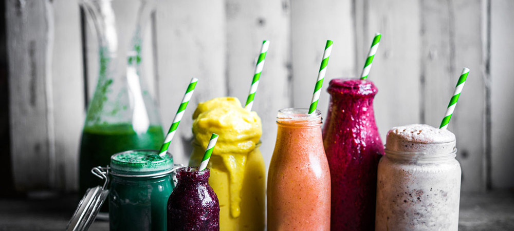 Variety of colorful smoothies on rustic wooden background